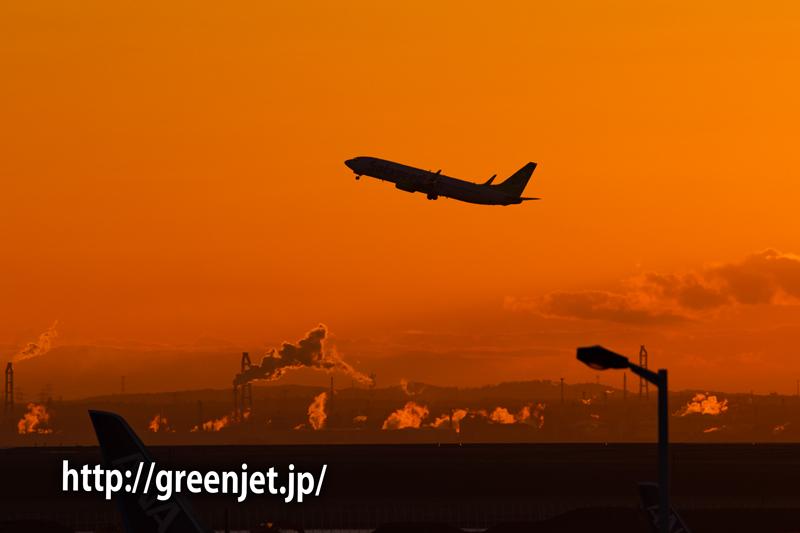 駐車場から望む朝焼けと飛行機