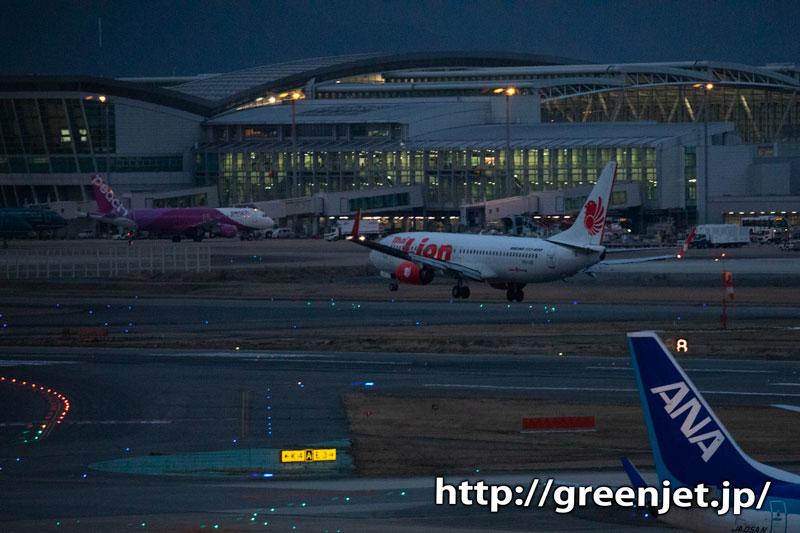 夜明けの福岡に降り立つ飛行機をホテルから