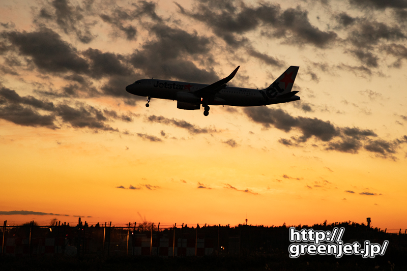 成田で飛行機~夕陽が反射するフェンスを絡め